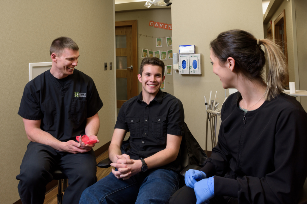 Young man conversing with Sensational Smiles team